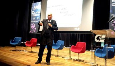 Homem com microfone em palco com seis poltronas azuis e vermelhas
