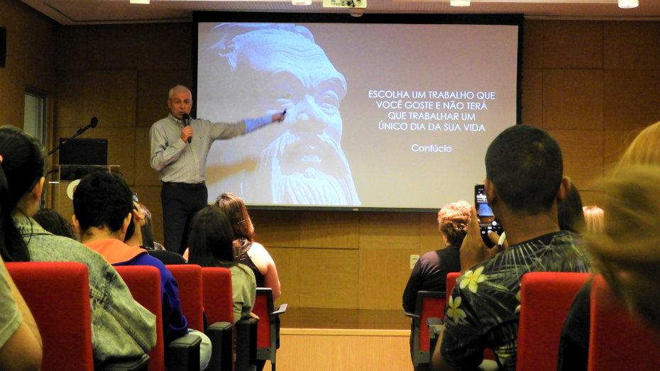 do ponto de vista da plateia, palestrante mostra slide com estátua chinesa