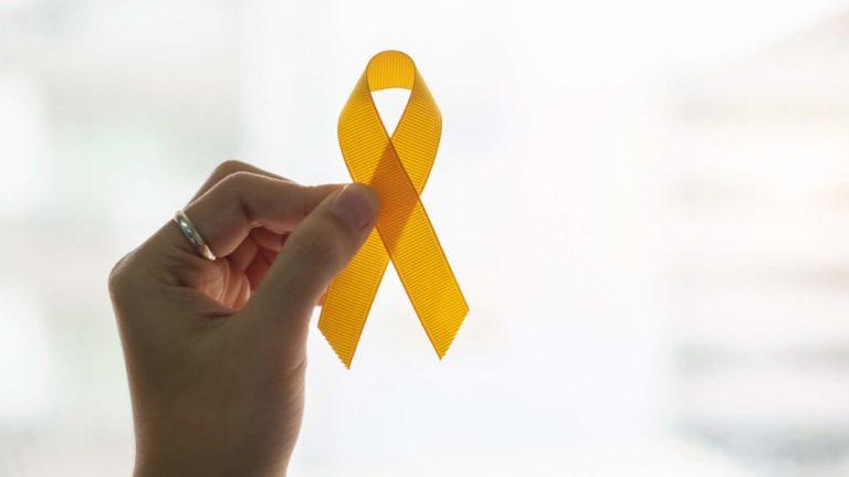 mão segurando laço amarelo com a ponta dos dedos