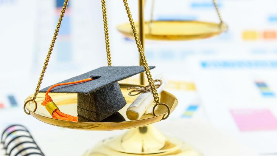 Na imagem vemos um capelo em destaque em cima de uma balança, símbolo do curso de Direito