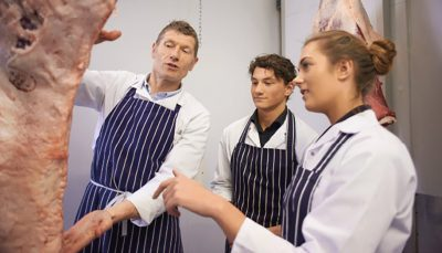 Homem ensina dois jovens sobre peça de carne em açougue