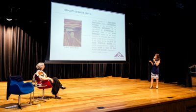 Duas mulheres em palco, uma sentada em cadeira enquanto a outra faz apresentação de slides em telão