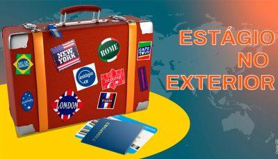 """Uma mala de viagem retangular cheia de adesivos com nomes de países e um logo do CIEE está à esquerda da imagem. E no lado direito, estão as palavras """"Estágio no exterior""""."""