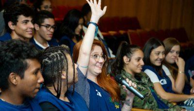 Garota de óculos com a mão direita levantada numa platéia com um microfone na mão esquerda