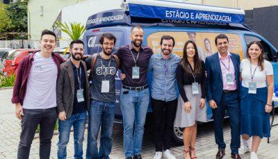 oito pessoas posando de frente para foto, a frente de uma van azul