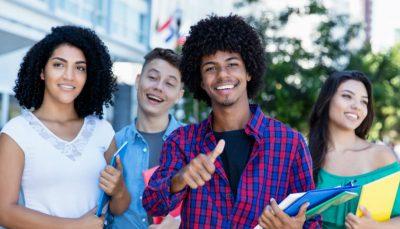 Jovens com pasta e sorrindo
