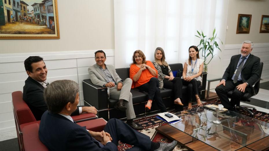 Quatro mulheres e quatro homens conversam em sala. Todas estão sentadas em sofás e poltronas