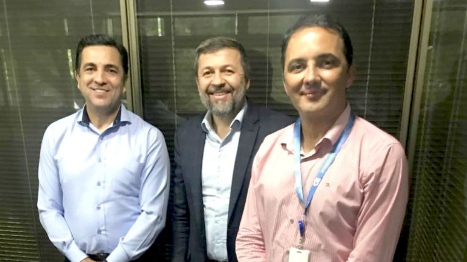 Três homens estão sorrindo para foto
