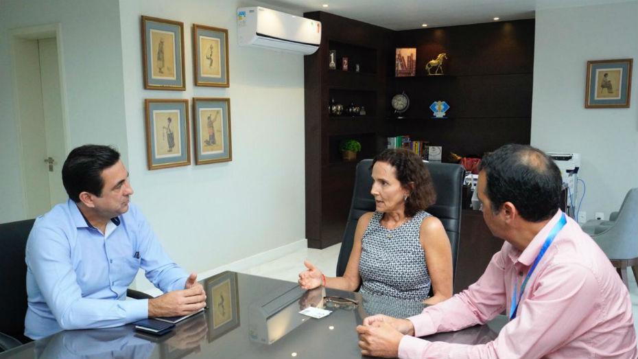 Dois homens e uma mulher conversam em uma mesa