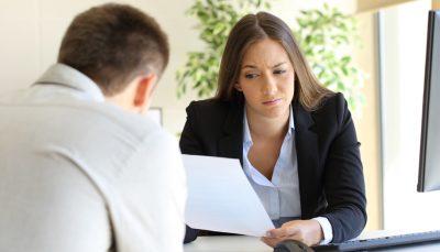 Mulher de cabelo comprido avaliando um currículo diante um candidato
