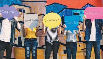 Cinco pessoas segurando balões de quadrinhos, em cada um está escrito Respeito, Igualdade, Cidadania, Trabalho e Protagonismo