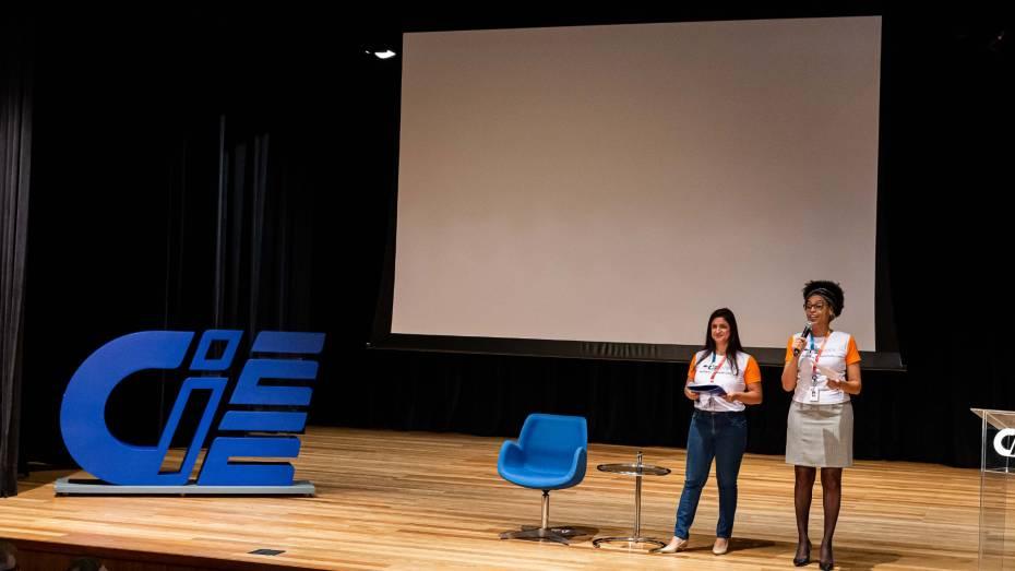Duas mulheres, no palco do CIEE, conversam com público de evento