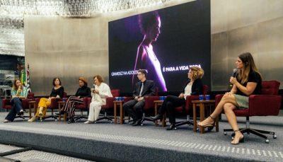 seis mulheres e um homem em palco, sentados em cadeiras