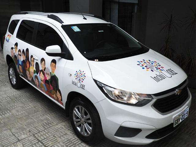 Carro branco do CIEE com vista frontal. A lateral do carro possui uma ilustração de pessoas de várias etnias.