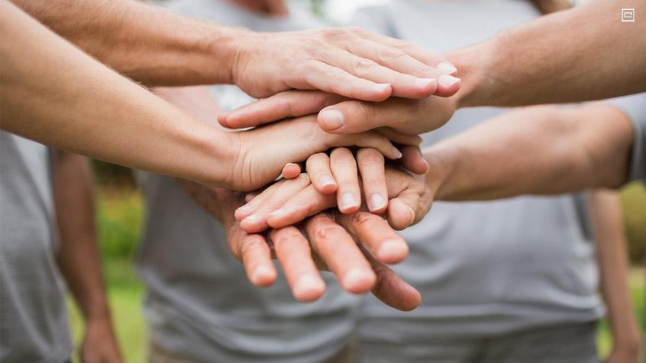 pessoas em roda colocando as mãos uma em cima da outra