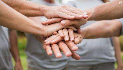 pessoas em círculo unindo as mãos ao centro