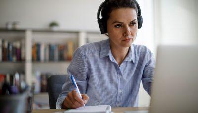 Mulher trabalhando com fone de ouvido, olhando para o computador e fazendo anotações
