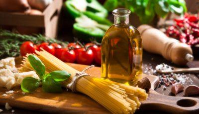 Em uma tábua sobre uma mesa aparecem uma porção de espaguete cru, axeite, tomates, manjericão, entr outros ingredientes