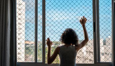 Menina, de cabelo encaracolado, está com as duas mãos apoiadas em uma tela da janela de aparamento