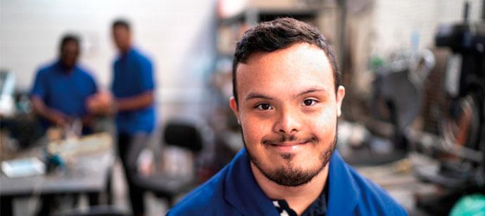 Um rapaz com uma camisa azul com síndrome de down sorrindo num ambiente de trabalho
