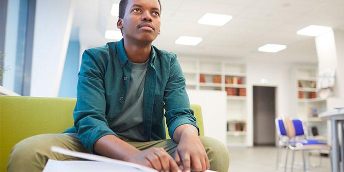 #PraCegover: Foto de um homem jovem negro em um ambiente escolar.  Ele olha para frente, usa uma camisa azul e uma calça bege. Está sentado em um sofá e na sua frente tem um livro sobre régua e faz leitura braille.