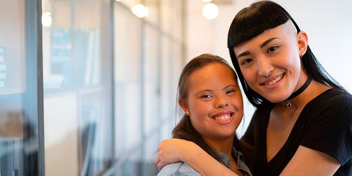 #PraCegoVer : foto com fundo desfocado de duas  moças se abraçando, ambas olham para frente e sorriem. Uma delas tem Síndrome de Down.