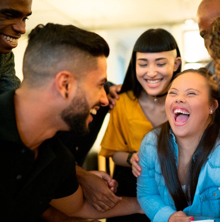 Reunião de pessoas num ambiente de trabalho, três homens e duas mulheres sorrindo