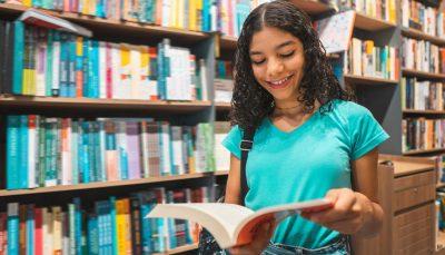 Uma jovem morena de cabelos encaracolados e com mochila preta nas costas sorri com um livro aberto em suas mãos. Ao fundo várias estantes de livro.