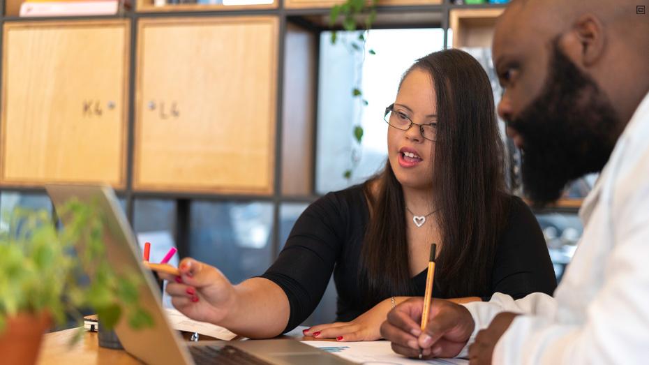 Mulher síndrome de down com cabelos longos lisos, castanhos e blusa preta está sentada ao lado de homem negro com barba. Os dois estão em um escritório e olhando para um notebook.
