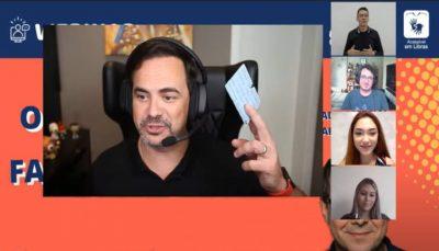 Frame do webinar, Em destaque na imagem, que reproduz a tela do computador, está o humorista Carioca com sua carteirinha do CIEE na mão. Em destaaques menores, à direita da tela, estão os demais participantes e interpréte de Libras