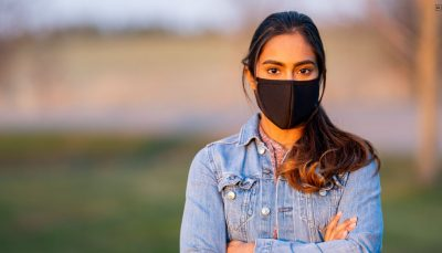 Jovem de cabelo longo, castanho, preso, posa para foto de braços cruzados e com uma máscara no rosto. O fundo está desfocado.