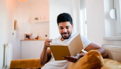 Homem preto, de cabelo encaracolado e barca, está sentado no sofá de sua casa com um livro aberto nas mãos