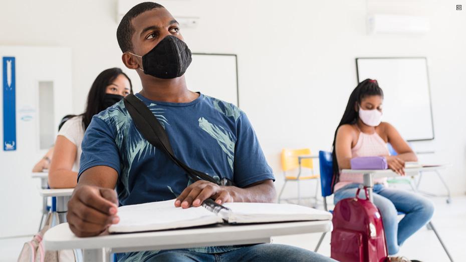 Estudante usando máscara sentado em uma poltrona universitária, ao fundo duas estudantes também usando máscara