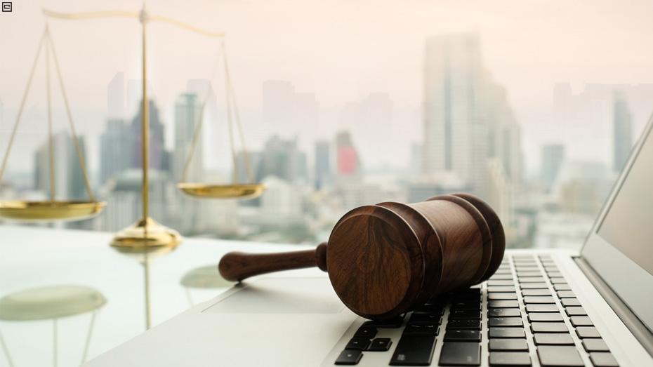 Martelo da justiça sobre o teclado de um notebook, com balança dourada e prédios ao fundo