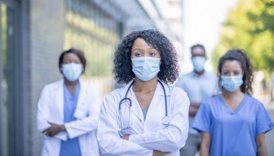 Mulher preta com cabelo encaracolado, na altura do ombro, solto. Está com máscara, vestida de jaleco, com braços cruzados e estetoscopio no pescoço. Ao fundo da imagem, desfocadas, é possível ver mais duas mulheres negras e um homem negro usando máscara e com roupa de hospital.