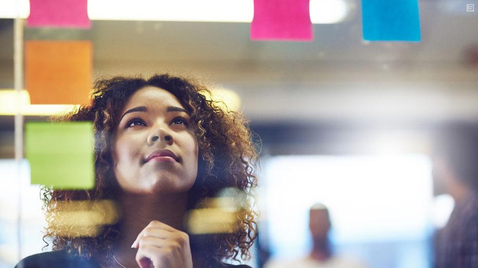 Mulher negra com cabelos encaracolados, na altura dos ombros, vestindo uma jaqueta jeans, olha para uma parede de vidro com post its coloridos