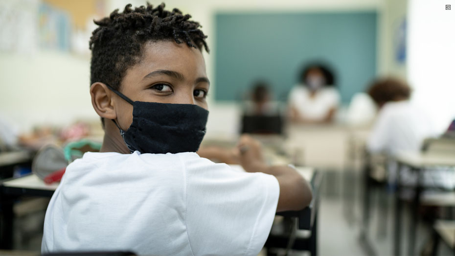 Menino negro com cabelo encaracolado curto veste uma camiseta branca e usa uma máscara de tecido preto que cobre a boca e o nariz. Ele está de costas e apenas com o rosto virado para a foto. Ao fundo é possível ver uma sala de aula.