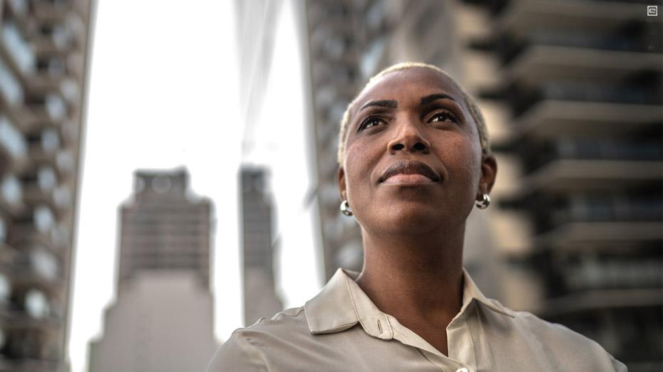 Mulher preta, de cabelo raspado e camisa branca está olhando para o céu com olhar compenetrado. Ao fundo da foto estão prédios desfocados.