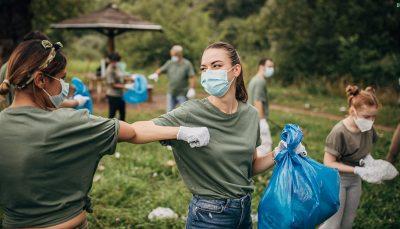 Uma mulher, branca, com cabelo preso, usando máscara e segurando um saco de lixo cumprimenta outra mulher batendo um cotovelo contra o outro. A segunda mulher, morena, com cabelo preso, vestindo camiseta verde e jeans, está de costas. Atrás da para ver algumas pessoas, em uma área verde, recolhendo lixo.