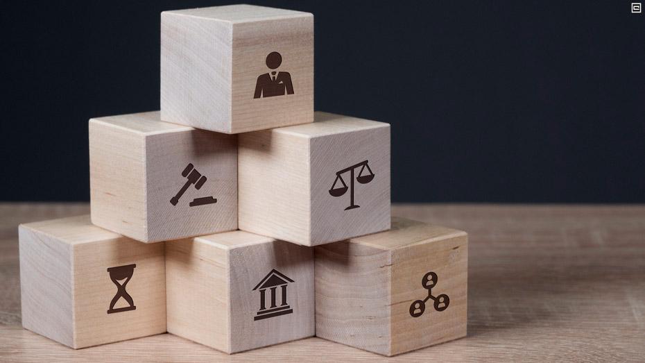 Seis blocos de madeira, formam uma pirâmide, cada um deles tem uma imagem que remete ao Direito