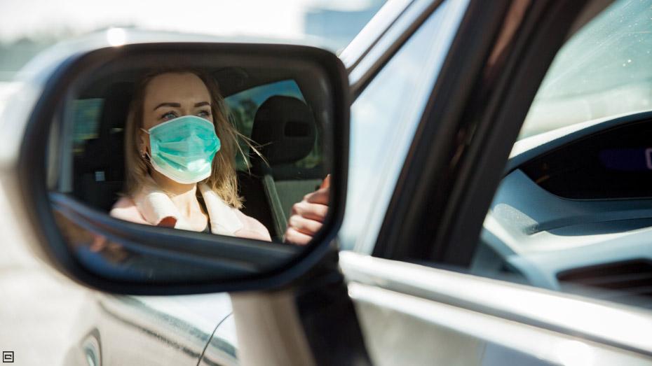 Mulher loira, com camisa rosa, está dirigindo um carro e é possível ver sua imagem refletida no retrovisor