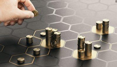 Moedas douradas posicionadas em um tabuleiro com marcações hexagonais que lembram um tabuleiro de jogo