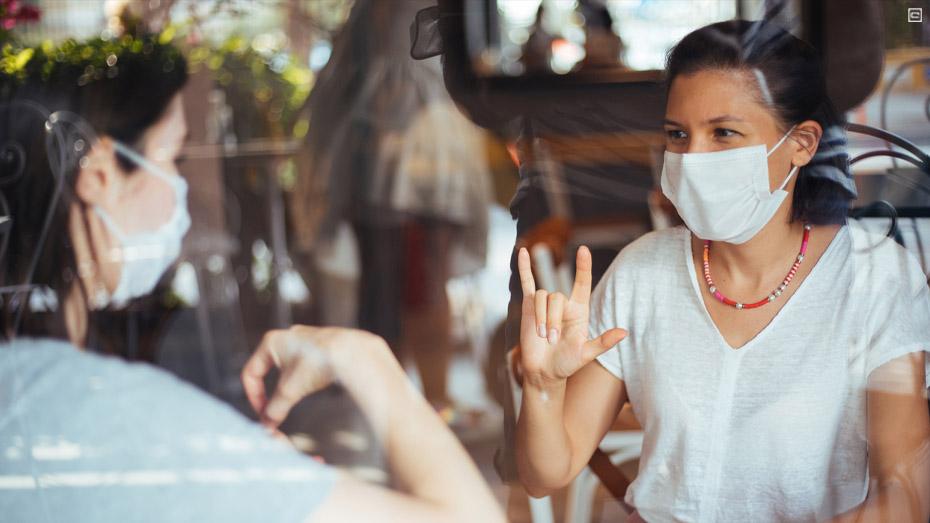 Duas mulheres de máscara conversado por linguagem de sinais