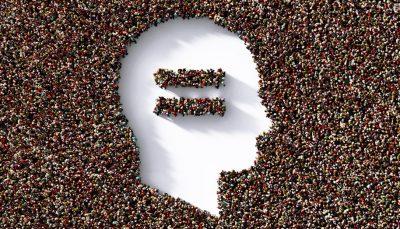 Ilustração de uma cabeça com um sinal de igual inserido. Ao fundo, uma multidão dá o contorno do desenho, mesmo recurso utilizado no sinal de igual