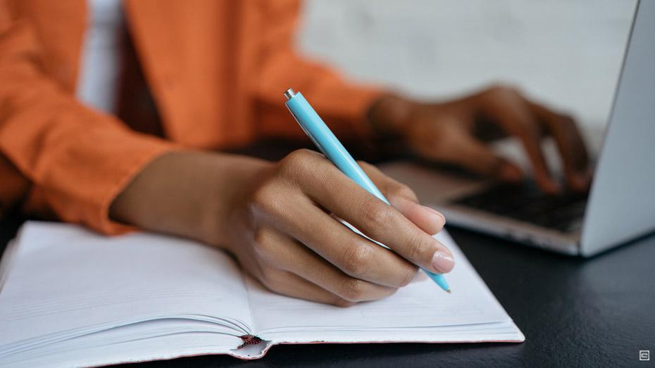 Imagem destaca mão de uma mulher negra escrevendo em um caderno sobre uma mesa, ao fundo é possível ver que ela está com a outra mão em um notebook