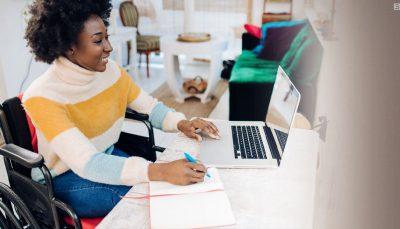 Na imagem uma mulher negra cadeirante está sentada à mesa com um notebook aberto