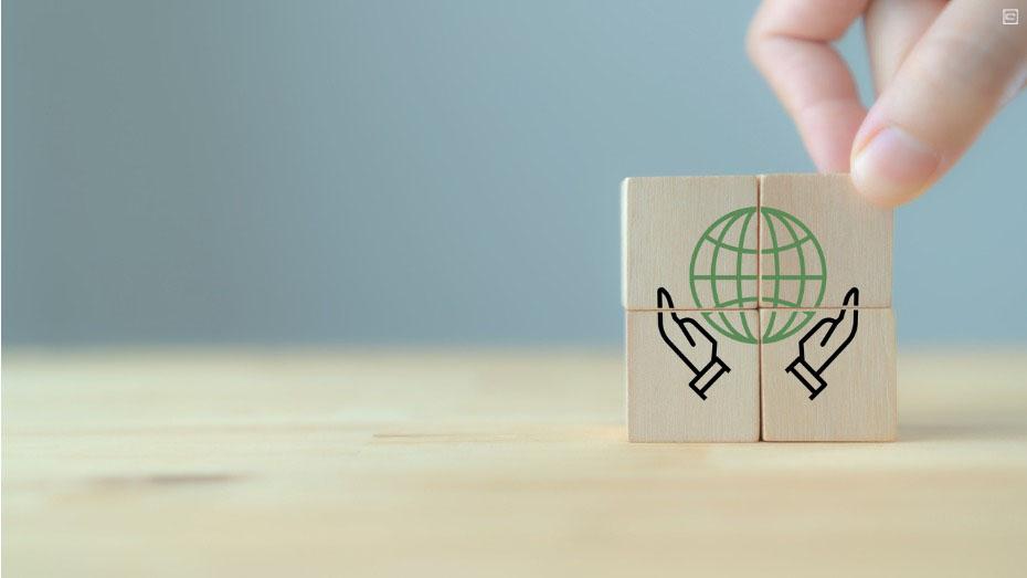 Foto que mostra pequenas peças de madeira formando o desenho do globo com mãos abaixo