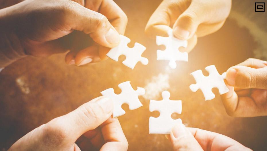 Peças encaixando um quebra-cabeça com cinco mãos iluninadas